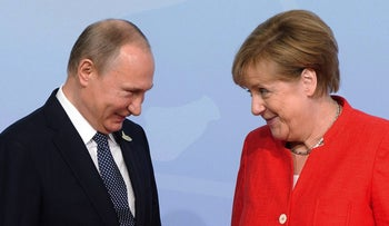 Russian President Vladimir Putin is greeted by German Chancellor Angela Merkel at the official welcoming ceremony at the G20 summit, Hamburg, Germany, July 7, 2017.