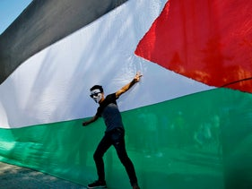 A Palestinian youth poses in front of his national flag during celebrations in Gaza City after rival Palestinian factions Hamas and Fatah reached an agreement on ending a decade-long split following talks mediated by Egypt on October 12, 2017. / AFP PHOTO / MOHAMMED ABED