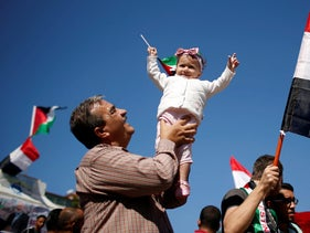 A girl is carried as Palestinians celebrate after Hamas said it reached a deal with Palestinian rival Fatah, in Gaza City, Gaza, October 12, 2017.