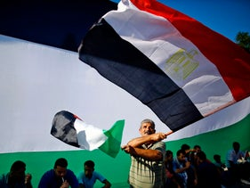 A man waves Egyptian and Palestinian flags as people celebrate after rival factions Hamas and Fatah reached an agreement, Gaza City, Gaza, October 12, 2017.