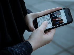 A woman follows news of U.S. President Donald Trump's decision to disavow the nuclear deal with Iran on her smartphone in Tehran, Iran October 13, 2017.