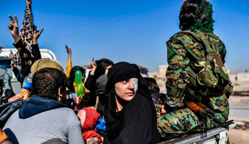 A Syrian woman looks back as civilians gather on the western front after fleeing the center of Raqqa, Syria, October 12, 2017.
