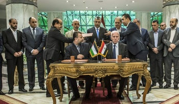 Hamas's new deputy leader Salah al-Arouri (seated L) and Fatah's Azzam al-Ahmad (seated R) sign a reconciliation deal in Cairo on October 12, 2017