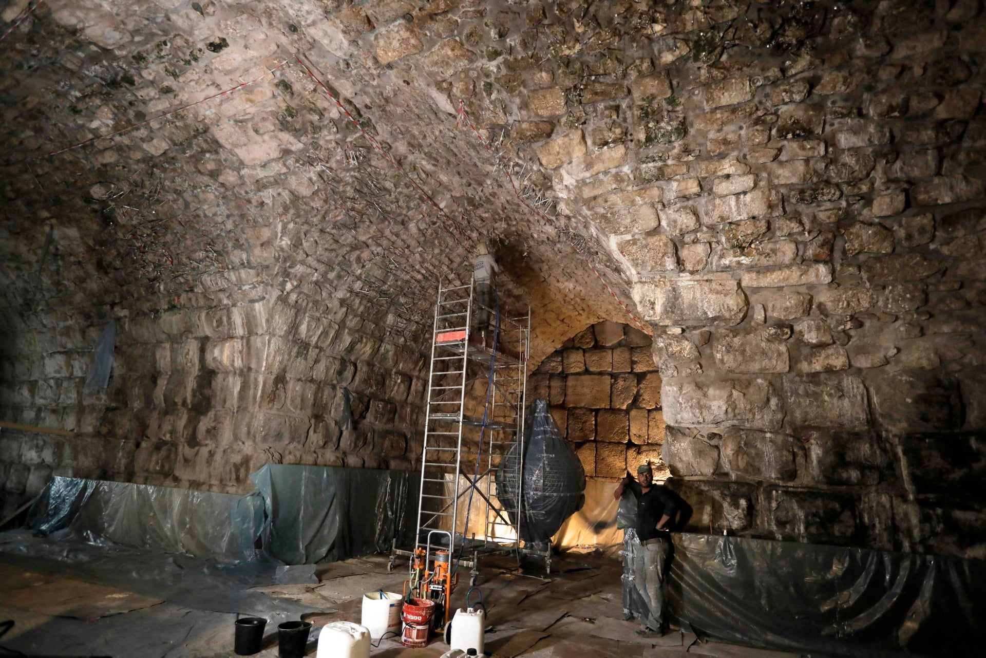 Workers restore a ceiling of the Western Wall tunnels near the site where Israeli Antiquity Authority recently discovered an ancient roman theatre from the second sanctuary in Jerusalem's Old City on October 16, 2017.