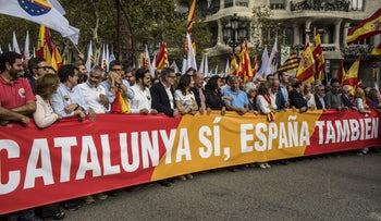 """Demonstrators hold a banner reading """"Catalonia yes, Spain too"""" in support of Spanish unity during a march in Barcelona, October 12, 2017."""