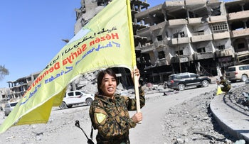 A Syrian Democratic Forces (SDF) commander, waves her group's flag at the iconic Al-Naim square in Raqa on October 17, 2017.