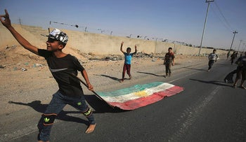 An Iraqi boy drags a Kurdish flag as Iraqi forces advance towards the centre of Kirkuk during an operation against Kurdish fighters on October 16, 2017