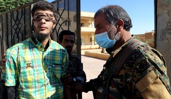 Members of Syrian Democratic Forces escort a blindfolded civilian detainee suspected to be a member of Islamic State militants in Raqqa, Syria October 12, 2017.