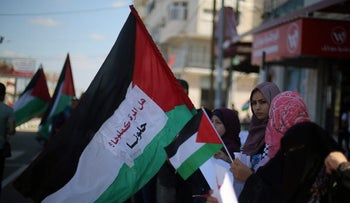 Women hold Palestinian flags as they celebrate after rival Palestinian factions Hamas and Fatah signed a reconciliation deal, in the central Gaza Strip October 12, 2017.