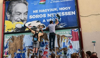 Activists from the Egyutt (Together) party tear down an ad by the Hungarian government against George Soros, in Budapest, Wednesday, July 12, 2017
