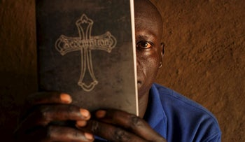 In this photo taken Monday, June 5, 2017, a refugee pastor from the Yei area of South Sudan, who spoke on condition of anonymity for fear of retribution from South Sudanese intelligence officials, covers his face with his Bible