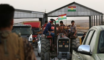 Iraqi families fleeing violence in the northern Kirkuk province cross a Kurdish checkpoint in Altun Kupri, the capital of the autonomous Kurdish region of northern Iraq on October 16, 2017.