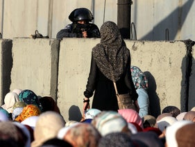 Palestinian woman looks at member of Israeli security forces at Qalandia checkpoint. Palestinians wait to cross from West Bank to Jerusalem for Friday prayers at Al-Aqsa Mosque, July 3, 2015.