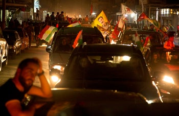 In this picture taken on September 25, 2017 and provided by Rojava Photo, Syrian Kurds citizens wave their parties and Kurdistan flags as they tour by their cars celebrating after the Iraqi Kurds in Erbil held the independence referendum, in Qamishli, north Syria. While Iraqג€™s Kurds have sparked confrontation with their drive for independence, Kurds in Syria are making major advances toward their more modest goal, entrenching their self-rule.(Baderkhan Ahmed, Rojava Photo via AP)