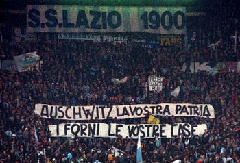 "In this Nov. 29, 1998 file photo, Lazio fans display banners from the stands reading ""Auschwitz is Your Homeland. The Ovens are Your Homes"" during a Serie A match between Lazio and AS Roma, at Rome's Olympic stadium. Lazio fans have a long history of racism and anti-Semitism but the Roman club's supporters established a new low on Sunday, Oct. 22, 2017 when they littered the Stadio Olimpico with superimposed images of Anne Frank, the young diarist who died in the Holocaust, wearing a Roma jersey"