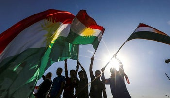 Iraqi Kurds wave flags of Iraqi Kurdistan during a demonstration outside the UN Office in Arbil, the capital of the autonomous region, on October 21, 2017, protesting against the escalating crisis with Baghdad