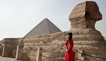 An Asian tourist posing in front of the Giza Pyramids in Egypt, August 7, 2017.