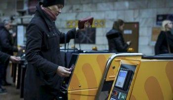 A passenger swipes a card against a terminal to ride the subway system in Kiev, Ukraine October 24, 2017