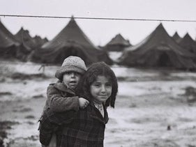 File photo: a young girl carries her brother at the Beit Lid Immigrant Camp, 1950.