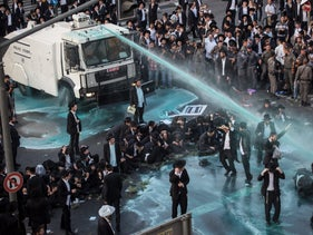 Members of the Israeli security forces spray water as they try to remove ultra-Orthodox Jews from blocking the road in a demonstration against Israeli army conscription in Jerusalem on October 23, 2017.