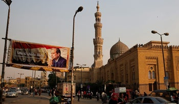 People walk by a poster of Egyptian President Abdel Fattah al-Sisi in downtown Cairo, Egypt October 17, 2017.