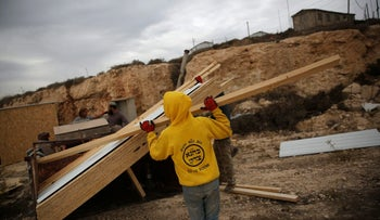 An Israeli youth builds wooden structures in the illegal outpost of Amona, West Bank, November 29, 2016.