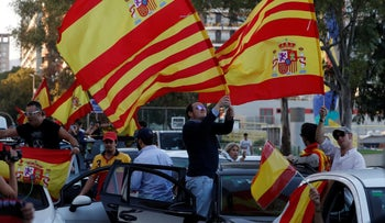 Pro-unity demonstrators wave the Spanish and Catalan flags as they gather in Barcelona, Spain, October 28, 2017.