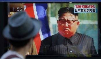 A man watches a TV news program on a public screen showing an image of North Korean leader Kim Jong Un while reporting North Korea's possible nuclear test in Tokyo, September.