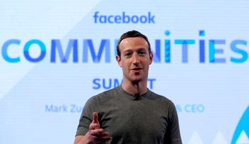 Mark Zuckerberg, shown wearing a grey short sleeved T-shirt and a neck mike, in front of a wall saying facebook COMMUNITIES Summit.