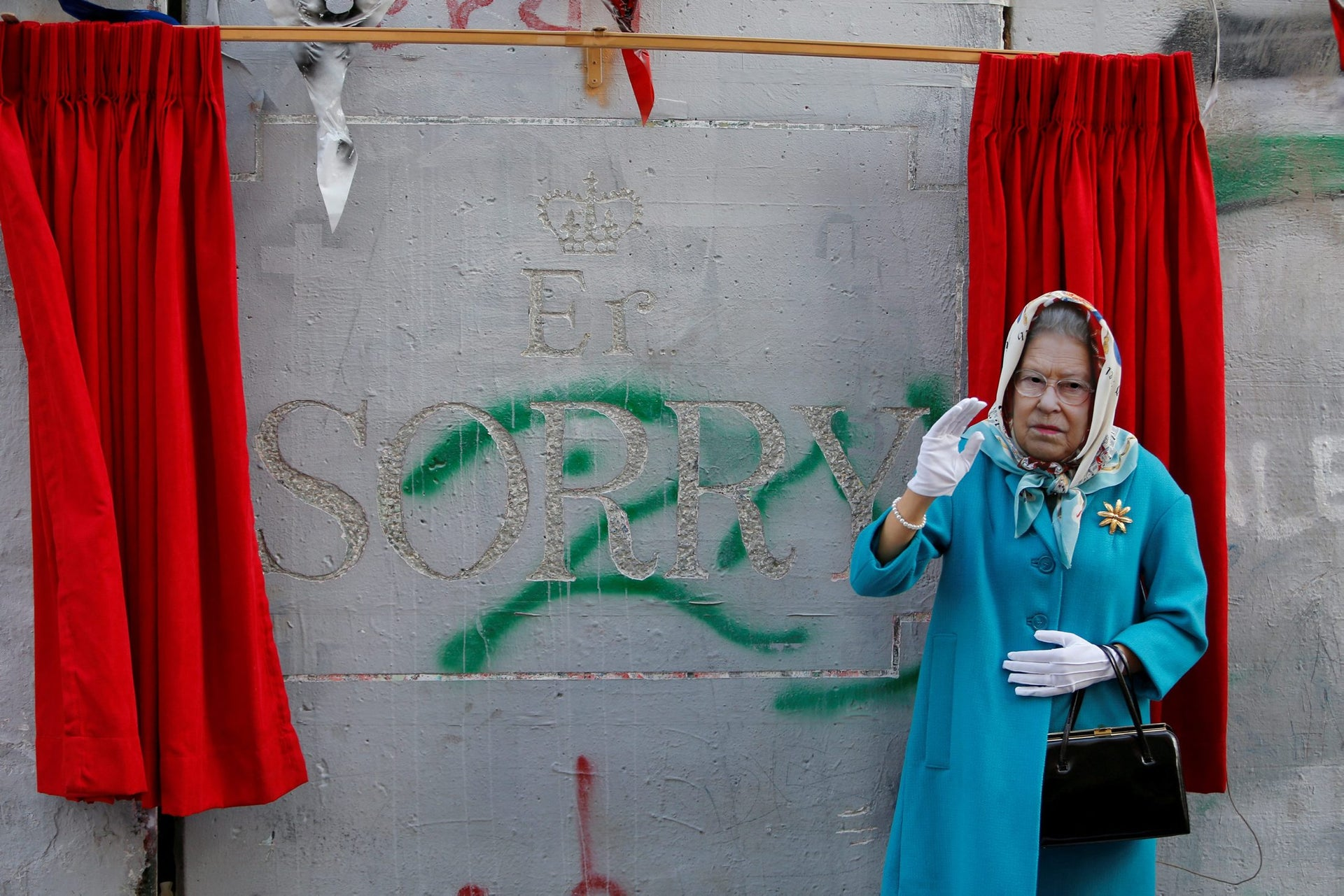 Someone dressed as Britain's Queen Elizabeth II gestures during an event organized by Banksy ahead of the anniversary of the Balfour Declaration, Bethlehem, West Bank, November 1, 2017.