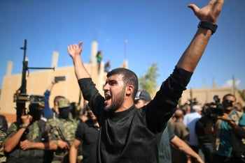 Mourner reacts as Islamic Jihad militants in Gaza hold their weapon at comrades' funeral.