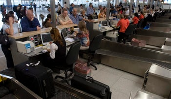 Travelers at Israel's Ben Gurion Airport check in for their flights.