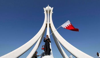 Protesters stand at the base of the Pearl Roundabout in the Bahraini capital of Manama, February 15, 2011