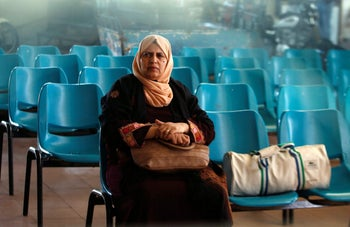 A Palestinian woman looks on as she sits at Erez crossing with Israel, in the northern Gaza Strip