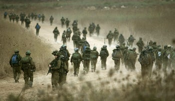 Israeli paratroopers walk along a dirt road as they make their way to a Lebanese village in southern Lebanon after crossing the border from northern Israel during the second Lebanon-Israel war. Aug. 12, 2006