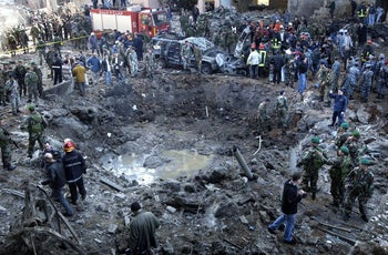 Rescue workers and soldiers stand around a massive crater after a Hezbollah bomb attack that killed former Prime Minister Rafik Hariri in Beirut, Lebanon. Feb. 14, 2005