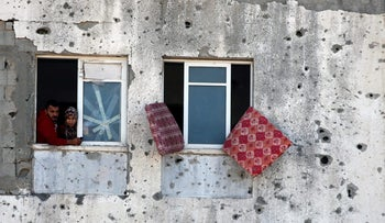 Palestinians look out of their apartment in a damaged residential building in Beit Lahiya town in the northern Gaza Strip November 1, 2017.