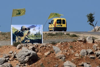 Hezbollah poster and flag on the Lebanese side of Israel's northern border, opposite the town of Metulla. 13 May 2017