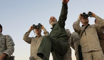 FILE PHOTO: This photo provided on Friday Oct. 20, 2017 by the government-controlled Syrian Central Military Media, shows Iran's army chief of staff Maj. Gen. Mohammad Bagheri, left, looks into binoculars as he visits the Iranian military near Aleppo, Syria.