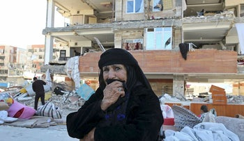 An earthquake survivor weeps as she sits in front of damaged buildings, in a compound which was built under the Mehr state-owned program, in Sarpol-e-Zahab in western Iran, Tuesday, Nov. 14, 2017