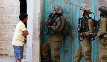 A Palestinian boy stands next to Israeli soldiers in the West Bank city of Hebron, 2014.