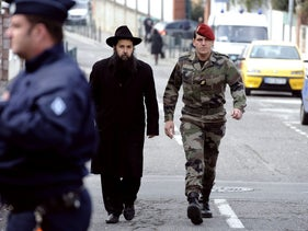 A rabbi flanked by a French paratrooper leaves the 'Ozar Hatorah' Jewish school in the French city of Toulouse, a day after a deadly shooting attack took place there, March 20, 2012.