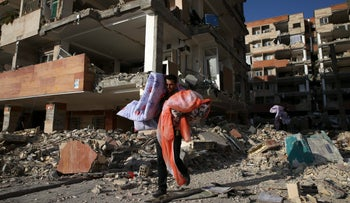 A man carries belongings of his brother's apartment damaged by an earthquake, in a compound which was built under the Mehr state-owned program Wednesday, Nov. 15, 2017