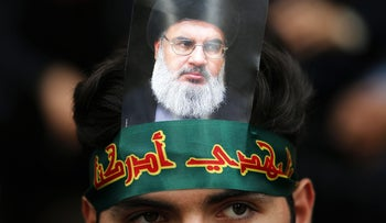 "(FILES) This file photo taken on October 01, 2017 shows a Hezbollah supporter displaying a picture of the Shiite movement's chief Hasan Nasrallah during a religious festival in a southern suburb of the Lebanese capital Beirut. Lebanon's Hezbollah, blamed by Saad Hariri for his shock resignation as premier, has grown over the three decades since its founding into a mighty army used by Iran to project regional influence. From Lebanon to Syria, Yemen, and Iraq, Hezbollah has matured into Iran's most useful ""tool"" -- thereby drawing the ire of Tehran's regional rival Riyadh, analysts say. / AFP PHOTO / ANWAR AMRO"