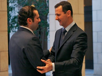 FILE - In this Dec. 19, 2009 file photo, Syrian President Bashar Assad, right, welcomes Lebanon's Prime Minister Saad Hariri, at Tishrin presidential palace in Damascus, Syria. Hariri who resigned from Saudi Arabia nearly two weeks ago has been caught in the crossfire between the regionג€™s two feuding powers -- Sunni Saudi Arabia and Shiite Iran. The 47-year-old who for years had tried to play a balancing act in Lebanon, with its delicate, sectarian-based political system, resigned in the most bizarre manner, throwing the countryג€™s and his own political future into the unknown. (AP Photo/ Bassem Tellawi, File)