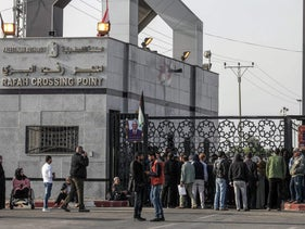 Palestinians queue as they wait for travel permits outside the gates of the Rafah border crossing with Egypt, under the control of the Palestinian Authority, in the southern Gaza Strip on November 18, 2017.