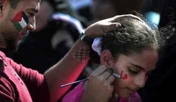 A man paints the colors of the Palestinian flag on a girl's cheek during a rally marking the 13th anniversary of the death of Fatah founder and Palestinian Authority leader Yasser Arafat, in Gaza City, Saturday, Nov. 11, 2017