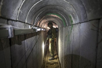 An Israeli army officer gives journalists a tour of a tunnel allegedly used by militants in Gaza for cross-border attacks, July 25, 2014.