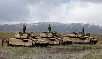 Israeli soldiers stand atop tanks in the Golan Heights near Israel's border with Syria March 19, 2014