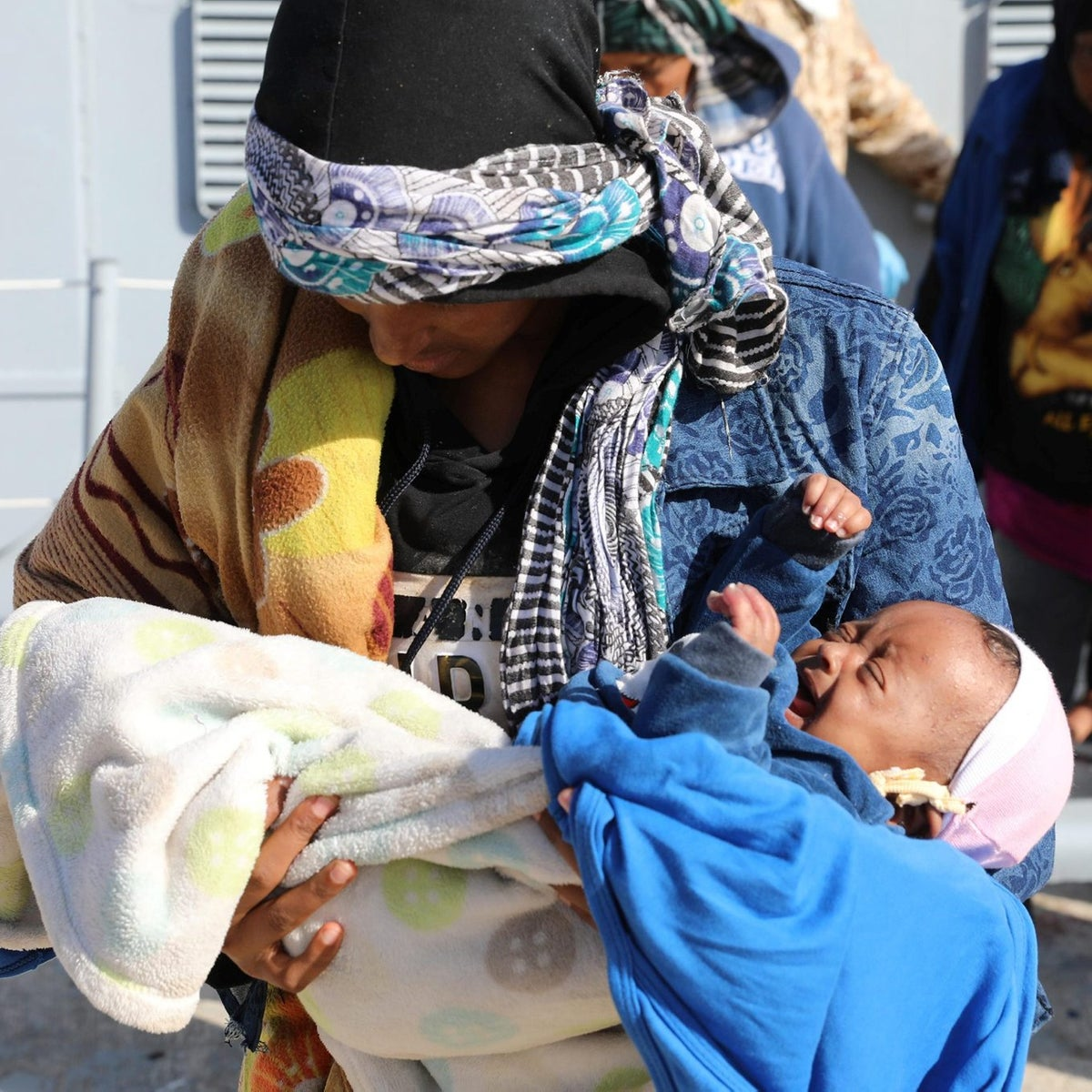 A migrant carries a baby at a naval base after they were rescued by Libyan coastal guards in Tripoli, Libya, November 24, 2017.